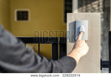 Man's Hand Pressing A Doorbell Button With Sunlight. Close Up Hand And Finger Visiter Ringing Buzzer