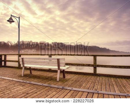 Misty Dusk On The Landmark Fishing Pier, Wooden Pier Railings. Wooden Mole Ends In Thick Mist
