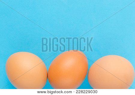 Three Brown Chicken Eggs Blue Background, Close Up.