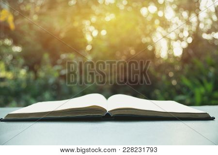 Open Book. Book Open On Old Wooden Table On Nature Background.
