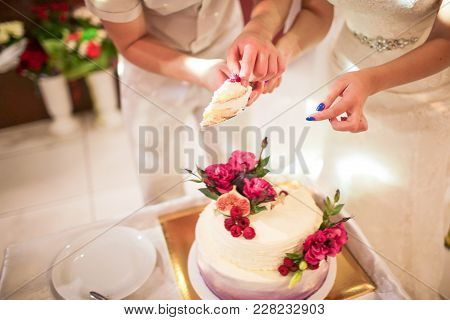 Elegant Pretty Young Bride And Groom Cutting The Wedding Cake.