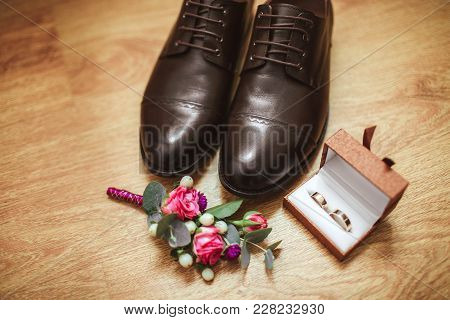 Men's Shoes Boutonniere And Wedding Rings In A Box, Against The Background Of A Wooden Floor. Weddin