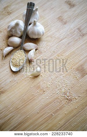 Garlic Bulbs, Cloves And Garlic Powder On A Wooden Background