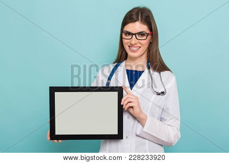 Portrait Of Female Brunette Doctor In White Coat And Eyeglasses With Braces On Her Teeth Holds Blank