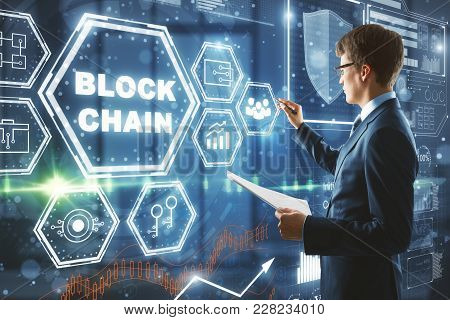 Businessman Drawing Abstract Block Chain Hologram On Blurry Office Background. Cryptography And Futu