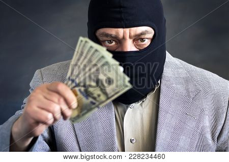 Businessman In Balaclava With Dololors In Hands On Dark Background. Crime. Theft. Not An Honest Busi