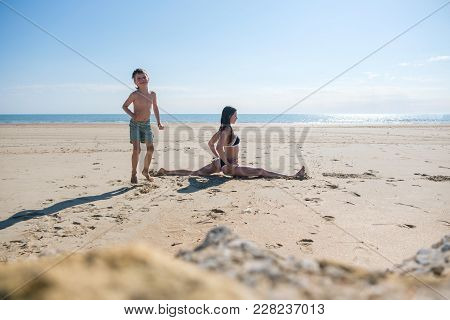 Mom In Blue Bikini Sit On The Twine On The Sandy Beach And Son Playing Near Her