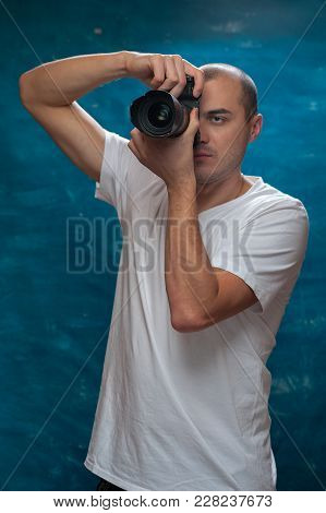 Smiling Middle-aged Man In White Shirt With Camera In His Hands Posing On Blue Background.