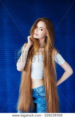Young Beautiful Woman In A White Shirt And Jeans With Very Long Natural Hair Near A Blue Wall In Lof