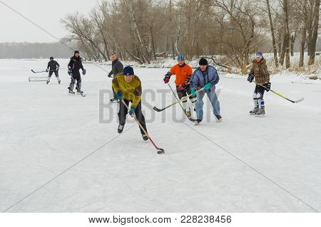 Dnipro, Ukraine - January 28, 2018: Group Of Different Aged People Playing Hokey On A Frozen River D