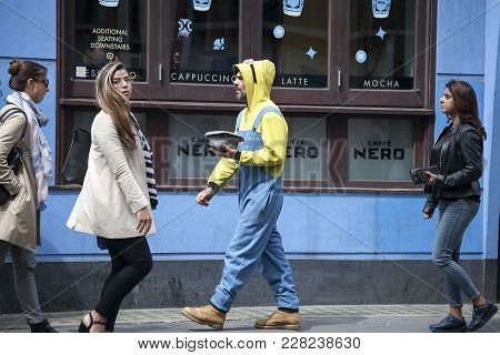 London, England - August 11 2017 Passers-by Walking Along The Street. A Beggar Man In A Yellow Suit