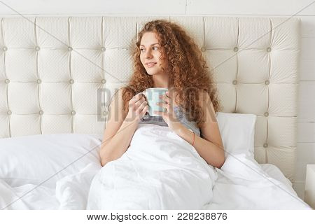 Pretty Young Woman With Curly Hair Has Morning Aromatic Coffee In Bed, Looks Pleasantly Away, Enjoys