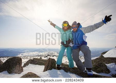 A guy and a girl snowboarders at the top of the mountain with their hands up, rejoice at the sun and the wind. Sheregesh resort. Russia.