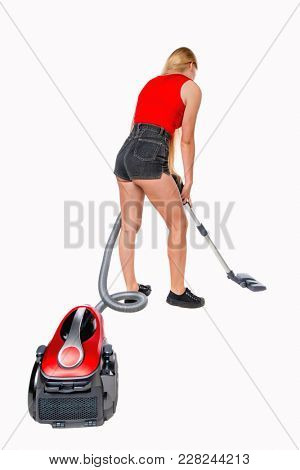 Rear view of a woman with a vacuum cleaner. She is busy cleaning. Rear view people collection.  backside view of person.  The girl in shorts with a vacuum cleaner cleans the floor.