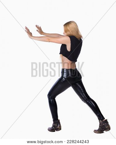 back view of woman pushes wall.  Isolated over white background. Rear view people collection. backside view of person. Blonde in leather pants shoves something in the side.