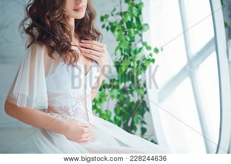Tenderness And Sensuality Concept. Beautiful Brunette Model Posing On Bed In White Lingerie. Sensual