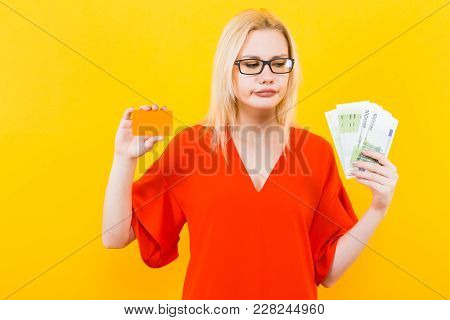 Portrait Of Disappointed Woman In Glasses And Red Dress Isolated On Yellow Background Hold Blank Cre