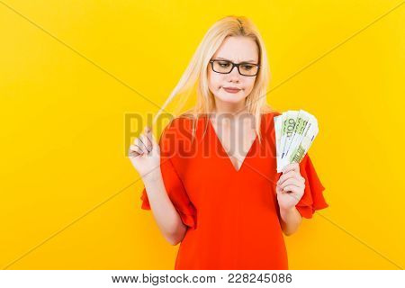 Portrait Of Unhappy Woman In Glasses And Red Dress Isolated On Yellow Background Hold Fan Of Euro Ba