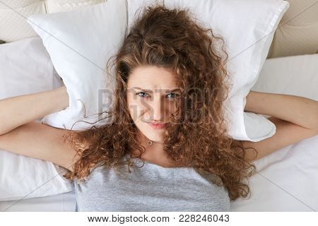 Depressed Frustrated Female Covers Ears With Pillow While Lies In Bed, Can`t Stand Someone`s Snoring