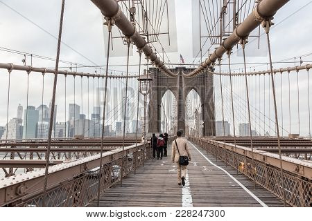 Man Walking On Pedestrian Path Across Brooklyn Bridge. New York City Manhattan Downtown With Skyscra