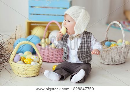 Funny Happy Baby Boy In Hat, Tie Bow And Suit Playing With Easter Eggs. Rabbit Banners On Wall