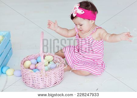 Cute Little Girl In Red Dress With Easter Eggs Sitting On Floor At Home