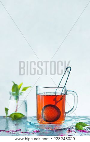 Glass Cup Of Herbal Tea With A Strainer, Petals And Fresh Green Leaves On A White Background. High-k