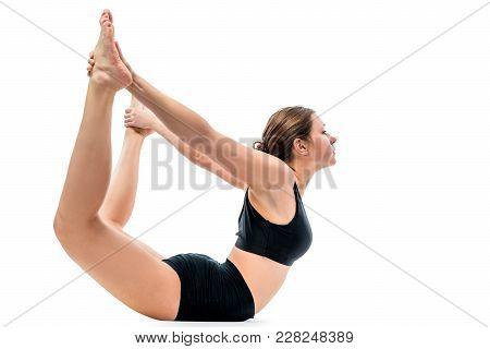 Athlete Engaged In Gymnastics In Black Sportswear, Shot Against White Background In Studio
