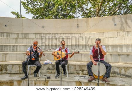 Arsos, Cyprus - October 8, 2017:  Cypriot Trio Of Musicians Playing Drum, Violin And Laouto.