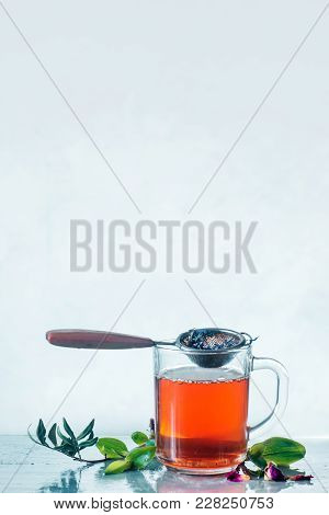 Herbal Tea In A Glass Cup With A Tea Strainer Light Background With Copy Space. High-key Spring Stil
