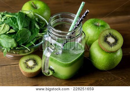 Freshly Blended Green Fruit Smoothie In Glass Jar With Straw. Spinach Aragula Green Apple Kiwi Detox