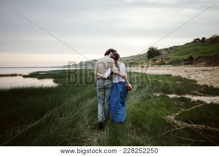 A Loving Couple Goes Embracing On The Grass By The Sea At Sunset