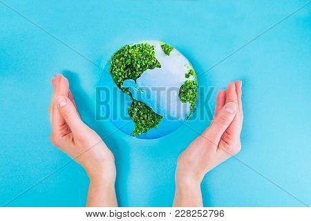 Top View Female Hands Holding Earth Paper And Green Sprouts Collage Model On Blue Background. Earth