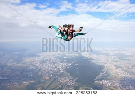 Skydiving Instructor And His Client Enjoying Tandem Skydiving
