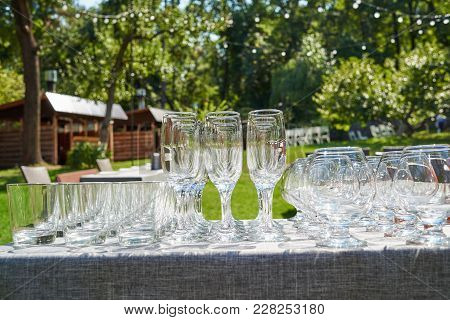 Rows Of Empty Glasses On Table Outdoors, Free Space. Set Of Sparkling Glassware. Crystal Glasses Rea