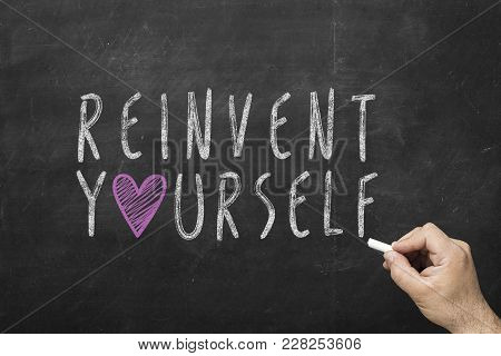 Hand Writing Reinvent Yourself On Black Chalkboard.