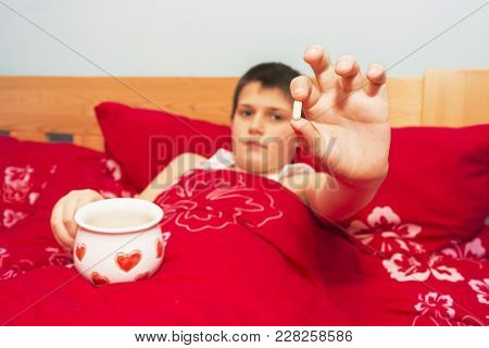 A Sick Boy Lying In Bed Holds A Cure In His Hand