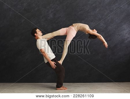 Young Couple Practicing Acroyoga On Mat In Gym Together. Woman Balancing On Man Legs, Doing Yoga Tru