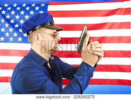 A Male Policeman Holding A Gun Over A Us Flag Satin - A Studio Shoot