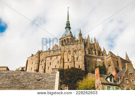 Low View Of Abbey With Statue Of Archangel Michael On Spire On Le Mont Saint-michel Island Famous Fo