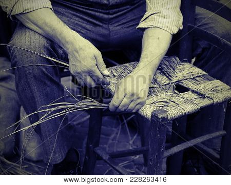 Man Mender Of Chairs While Repairing Old Chair With Vintage Effect