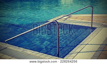 Swimming Pool With Ladder And The Steel Handrail In The Resort