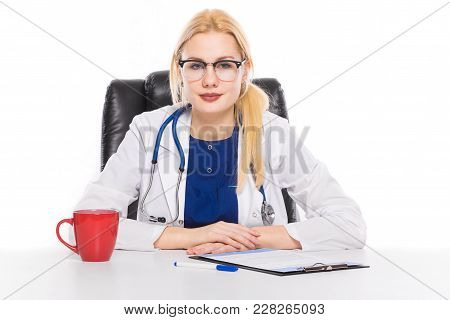 Female Doctor Or Head Physician In White Coat And Glasses With Stethoscope Sits In Leather Chair At