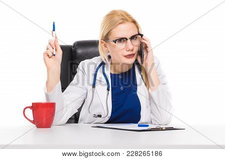 Female Doctor Or Head Physician In White Coat And Glasses With Stethoscope Sits In Chair At Table Wi