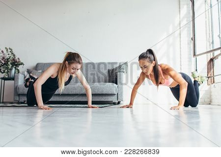 Two Fit Women Doing Push Up Exercise At Home.
