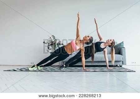 Fit Women Doing Side Plank Exercise Practicing Pilates At Home.