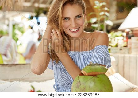 Cropped Shot Of Smiling Female Enjoys Exotic Fruit Cocktail, Dressed In Fashionable Blouse, Has Broa