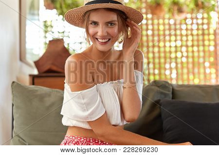 Photo Of Good Looking Young Female Wears Straw Hat, White Blouse, Demonstrates Bare Shoulders, Sits