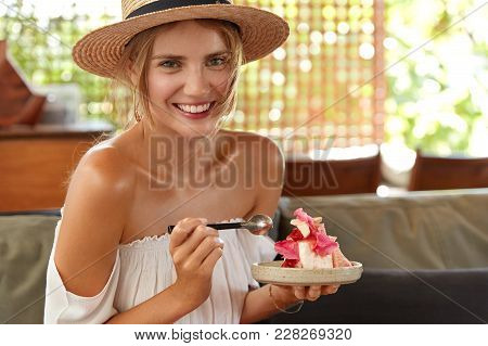 Indoor Shot Of Smiling Good Looking Female Wears Fashionable Clothes, Sends Free Time At Restaurant,