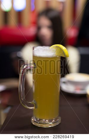 A Glass Of Unfiltered Beer With Lemon On The Table In The Cafe.